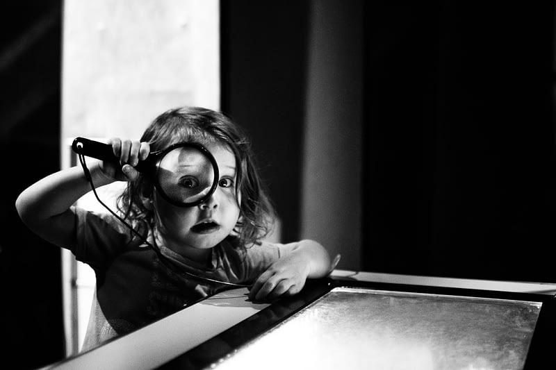 Kleines Mädchen das durch eine Lupe schaut, ähnlich wie beim SEO die Keyword Recherche und der Blick fürs Detail