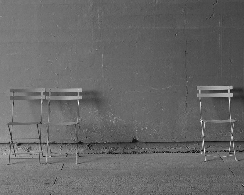Drei Stühle einer steht abseits von den anderen beiden, Symbol für Abgrenzung, die eigene Nische zu finden